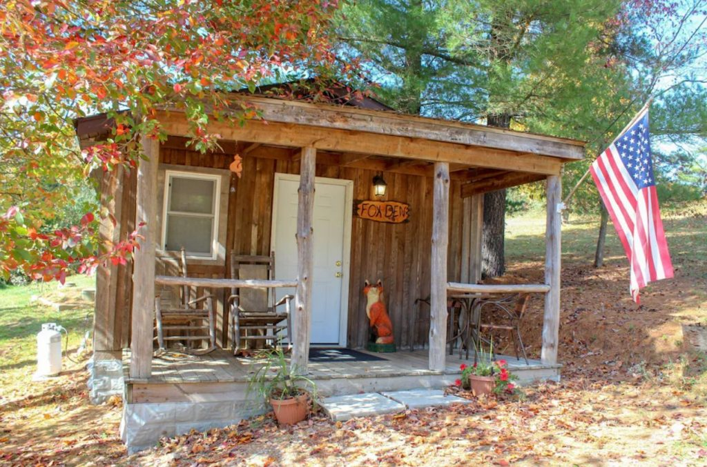 The exterior of a small wooden cabin. It has a small front porch with seating and a fox sculpture. There is an American flag hanging on the porch. Behind the cabin you can see trees with green and red leaves. There are dead leaves on the ground and a flower pot with red flowers near the porch.