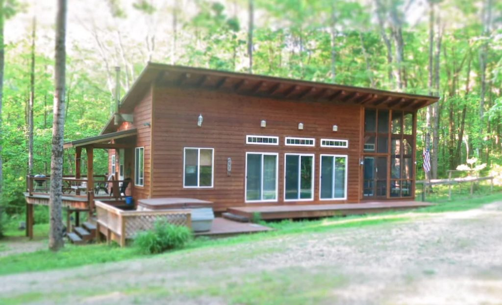 The exterior of a small narrow cabin in the woods. It has three sets of sliding glass doors and a small screened in porch. On the side of the cabin there is a deck with a hot tub, and another deck with seating and a grill. The cabin is surrounded by trees with green leaves and there is a gravel driveway in front of it.