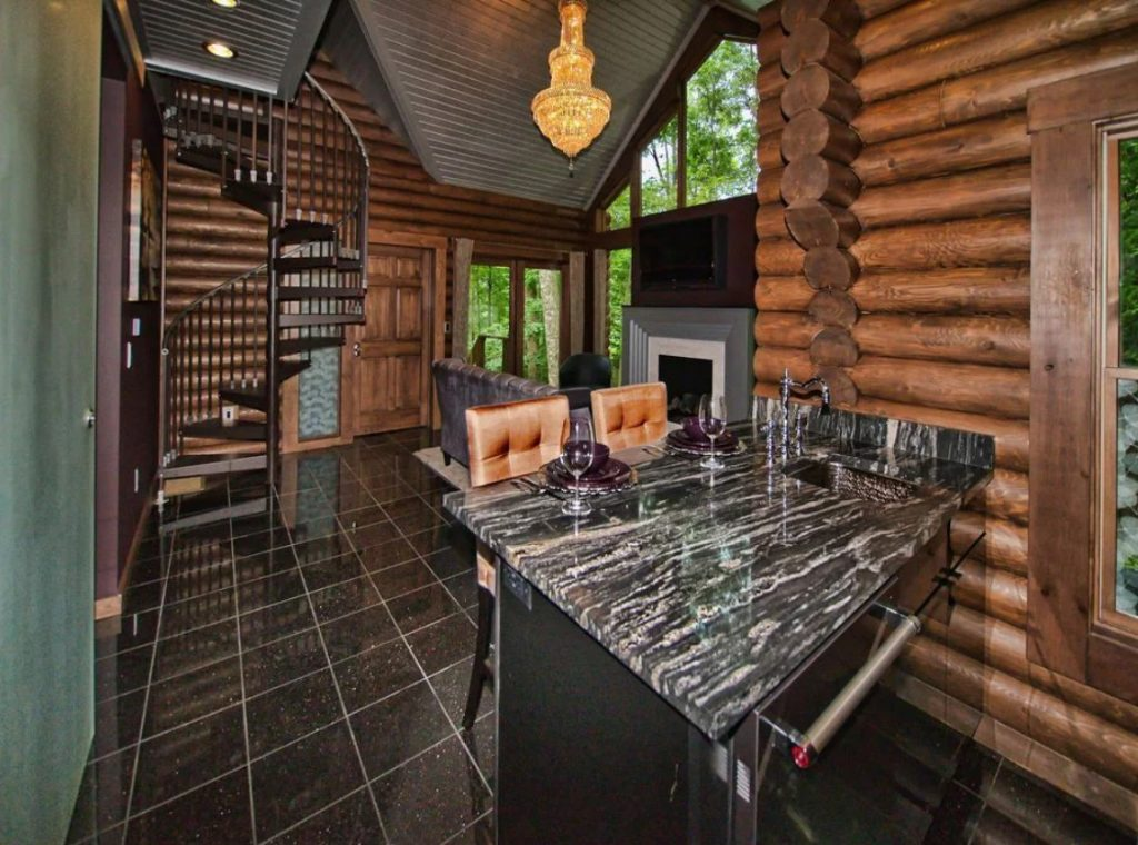 The interior of a fancy log cabin. It has marble countertops, a leather couch, a fireplace, a large chandelier, and a spiral staircase. It is one of the most unique cabins in Ohio.