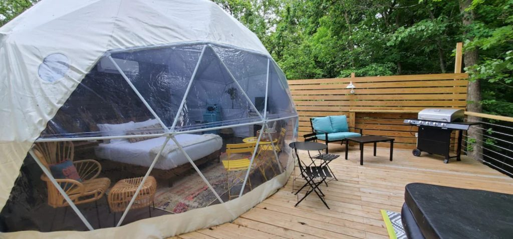 A white and see through dome on a large wooden platform in the woods. Through the clear areas of the dome you can see a bed and some chairs. On the platform there is some patio seating, a grill, and a hot tub. One of the best cabins in Hocking Hills