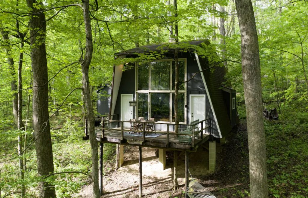 The exterior of a black retro style A-frame cabins in Hocking Hills. It has floor to ceiling windows with white trim, a lard deck, and is surrounded by trees.