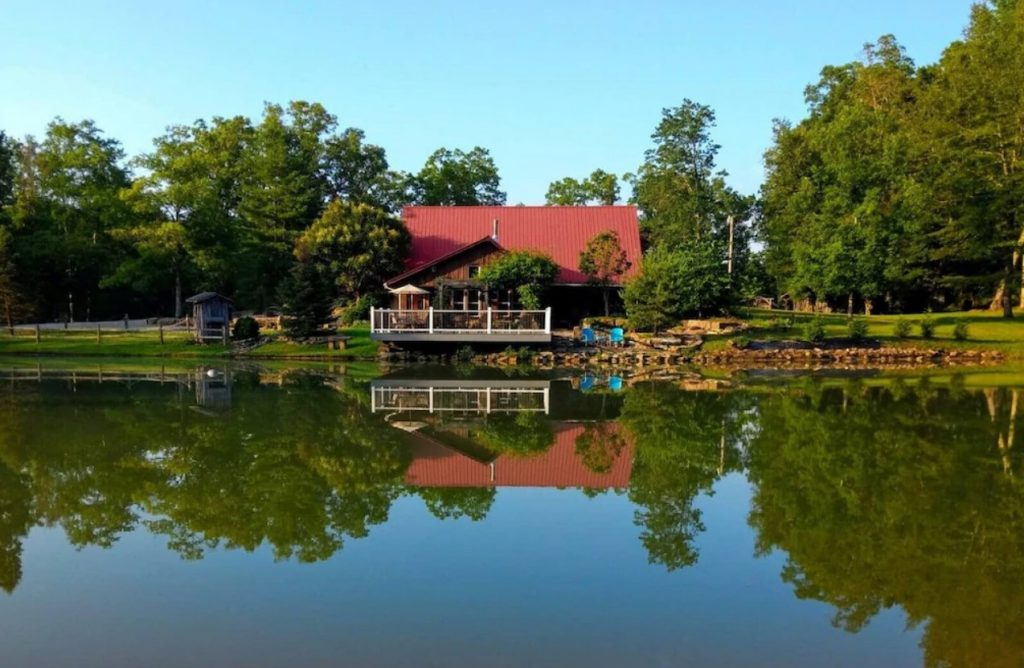 The exterior of a cabin with a red roof and a porch with white railing. It is sitting on the shore of a large pond or lake. The cabin is surrounded by a large green lawn and lots of trees.
