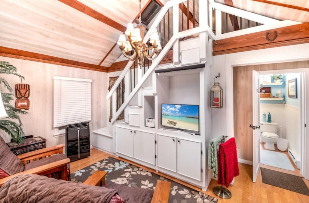 The interior living room of a small cabin in Ohio on Indian Lake. It has a loft, a built in cabinet under the stairs to the loft, and two chairs. The door to the bathroom is open and you can see the toilet.
