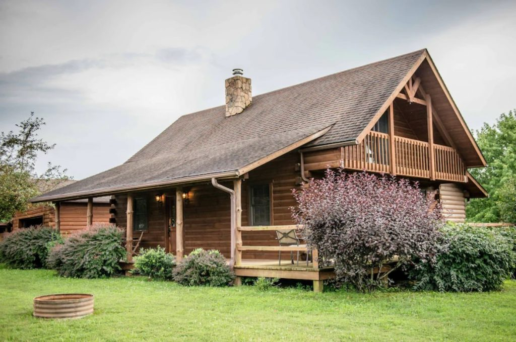 The exterior of a classic log cabin on a grassy lawn. There are shrubs with green and dark purple leaves surrounding the cabin. You can see a front porch with patio seating and a metal firepit in the yard. One of the best cabins in Hocking Hills