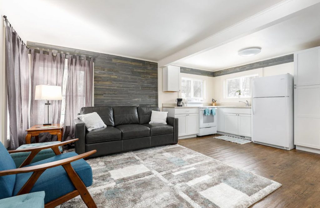 The interior of a tiny home in Traverse City Michigan. There is a dark leather couch against a fake distressed wood wall, a large carpet with grey, white and blue squares, and a blue chair. There is also a small kitchen with white appliances and cabinets and two windows.