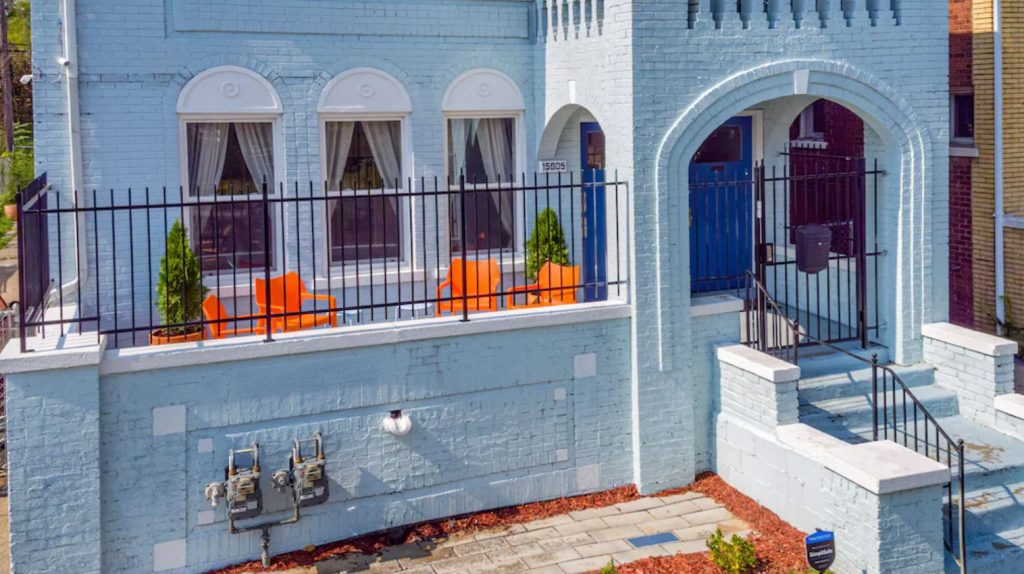 The front of a brick colonial home in Detroit. It is painted a pale blue-grey and has a gated front porch. On the porch you can see bright orange chairs, three tall windows, and bright blue doors. One of the best Michigan airbnb options