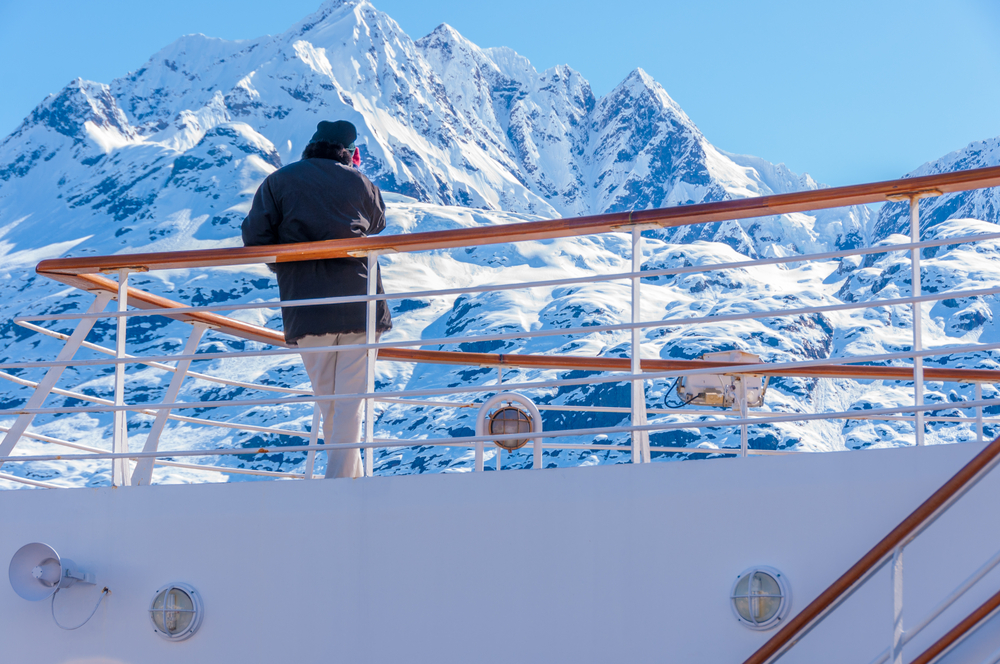 Man admiring snow covered mountain on deck of cruise ship. Jacket part of his Alaska cruise packing list.