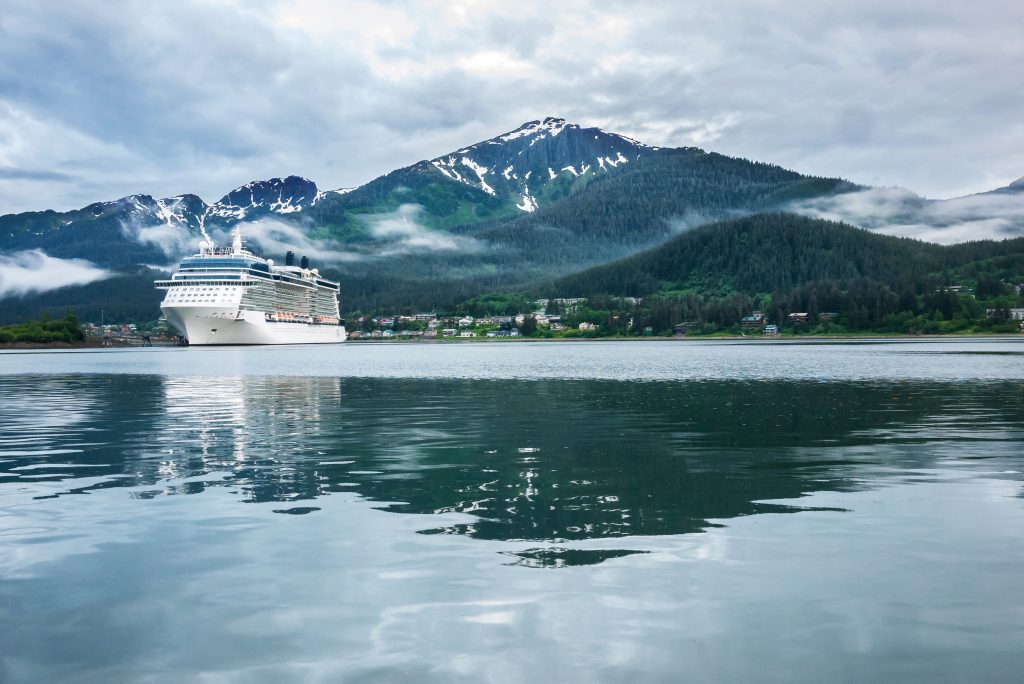 Alaska cruise ship in port with blue waters and snow capped mountains in background.