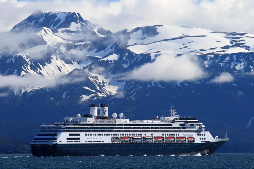 Large blue Alaska cruise ship sailing past snowcapped mountains.