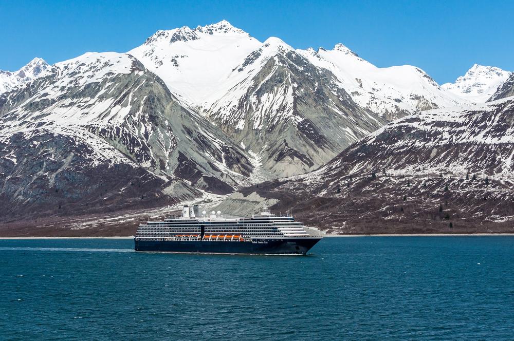 Blue Alaska cruise ship sailing past snow capped mountains