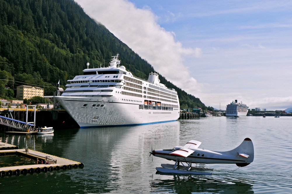Cruise ship in port with blue water plane landing on water in foreground.