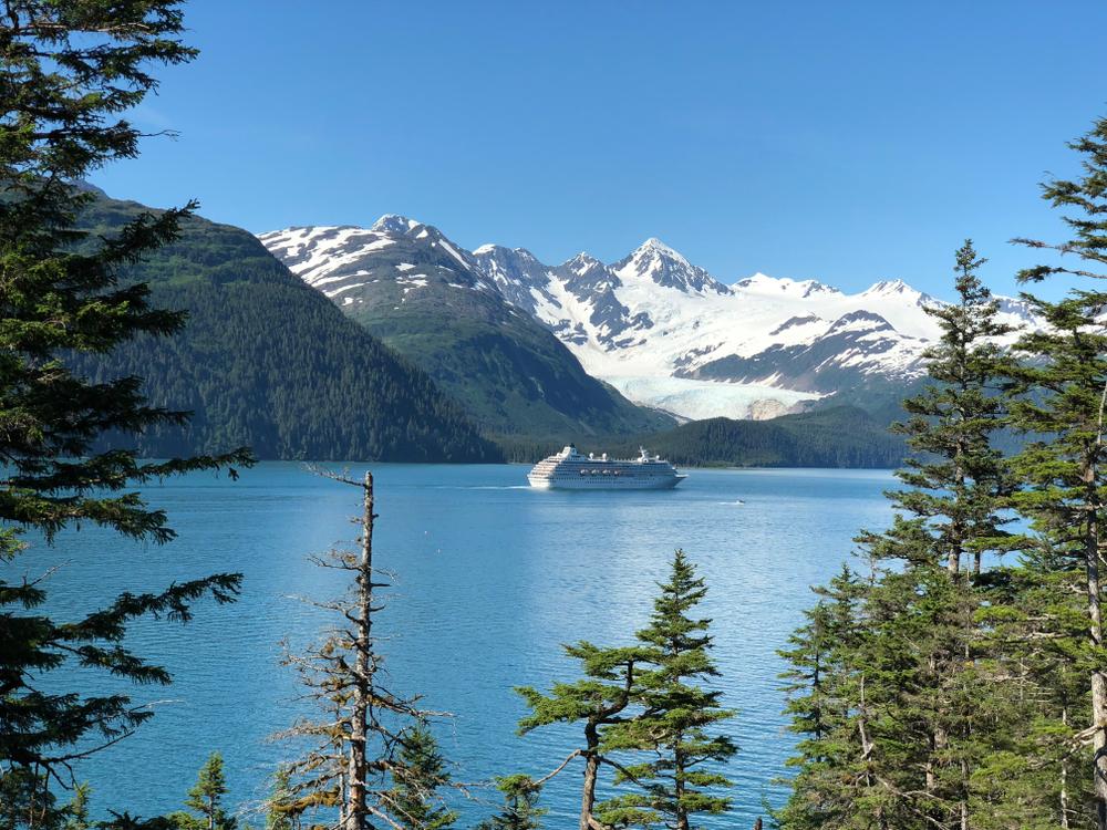 Cruise ship in Alaska sailing towards snow capped mountains Alaska Cruise packing list
