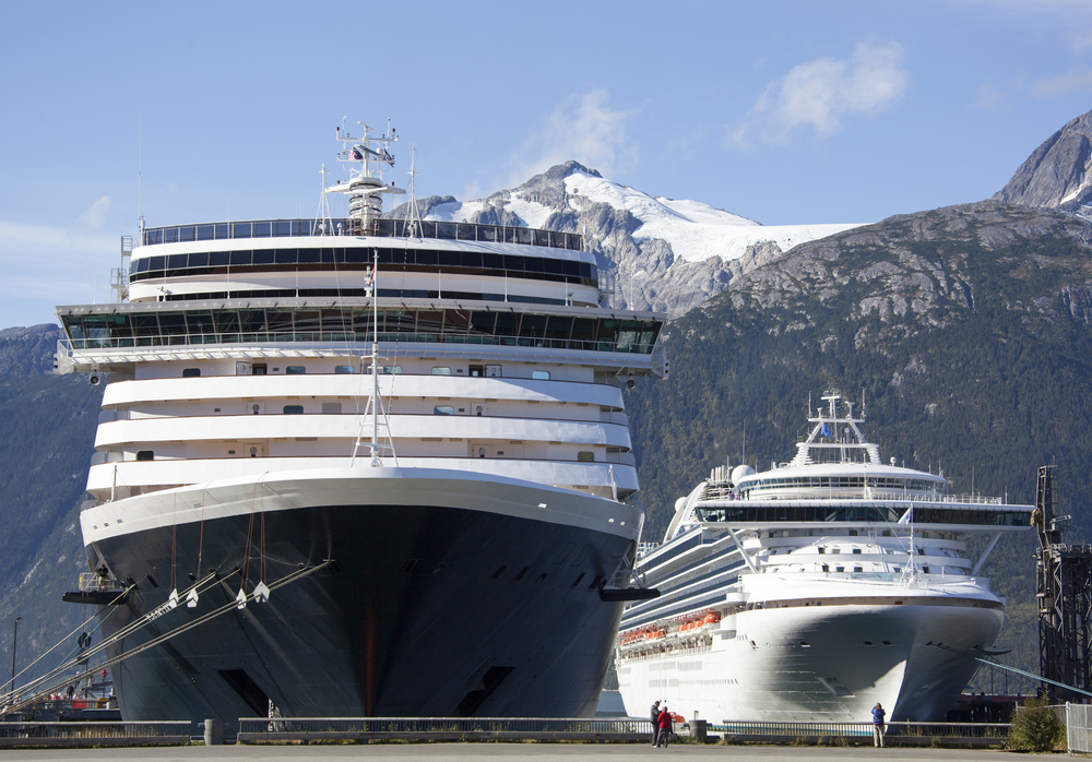 Cruise ships in Alaska at port surrounded by large Alaska mountains