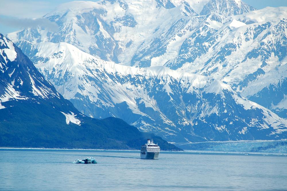 Alaska cruise ship dwarfed by gigantic snow capped Alaska mountains.