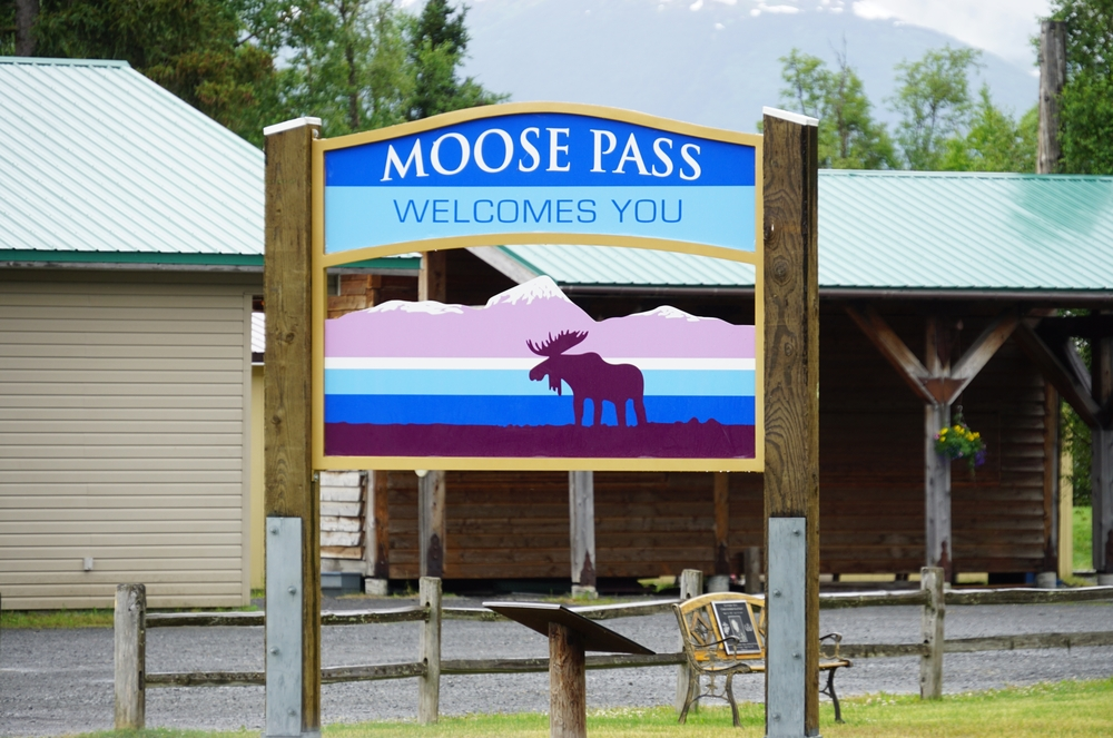 """Blue and purple sign that says """"Moose Pass weclomes you!"""" when driving from"""
