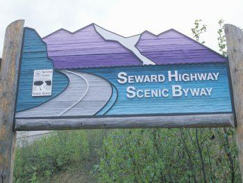 Blue and purple Alaska road sign signaling Anchorage to Seward