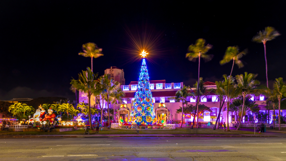A Christmas tree surrounded by palm trees in Oahu one of the Christmas vacations in the USA