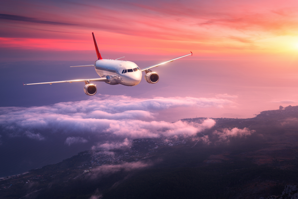 white passenger airline flying during sunset over clouds, with ocean below