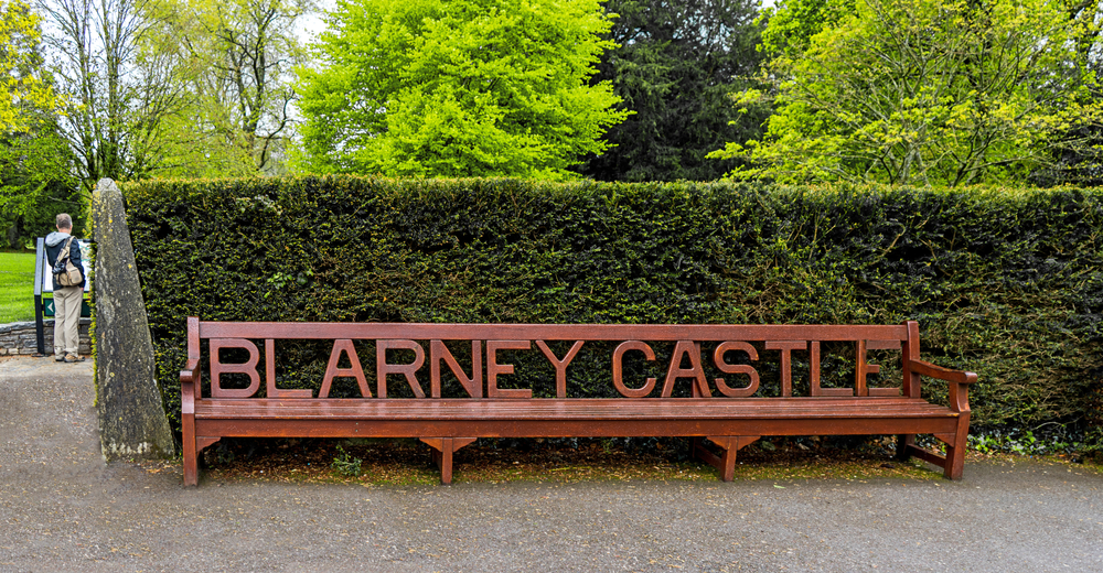 """Red bench with the words """"Blarney Castle"""" cut out on the back. Green hedge in background."""