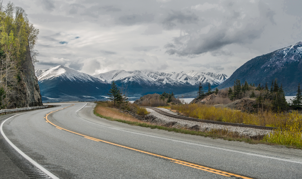 Seward Highway curves beneath cloudy skies with snowcapped mountains in background.