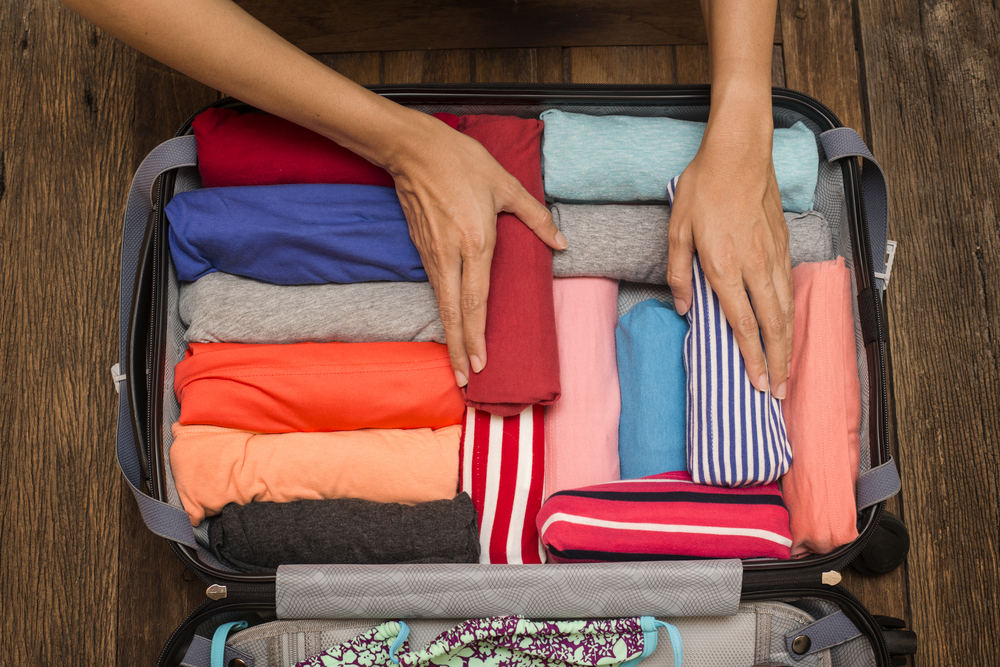 Female hands packing carry-on suitcase by rolling all clothes to be more efficient. How to pack lightly using only a carry-on