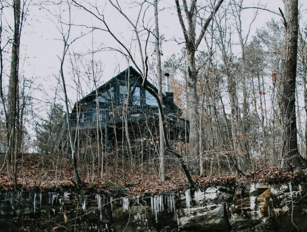 The exterior of a black cabin that is peaking through the trees in the woods. The trees have no leaves, there are dead leaves on the ground, and there is ice dripping down the stones on the hill in the woods where the trees are. The cabin has a wrap around deck and large windows.