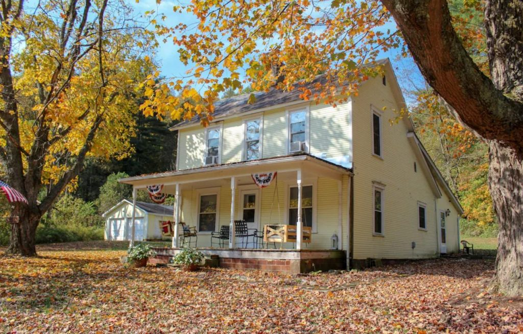 A yellow farmhouse with a front porch, a porch swing, patio chairs, and patriotic bunting hanging from the ceiling. The farmhouse is surrounded by trees with yellow, orange, red, and green leaves. There are dead leaves on the ground. It is one of the best Hocking Hills Airbnbs.