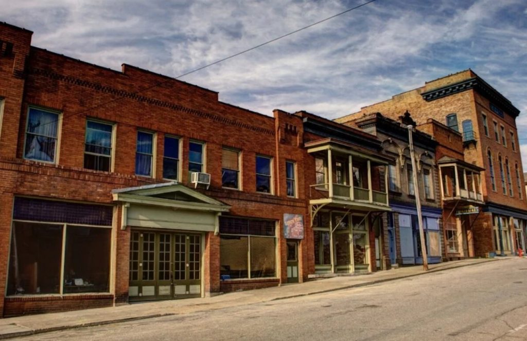 The exterior of a row of old buildings in a mining town in Ohio. The buildings were built in the early 1900s and are made of brick. They have lots of windows, sage green and cream trim, and some have upper decks. One of the best Hocking Hills Airbnbs.