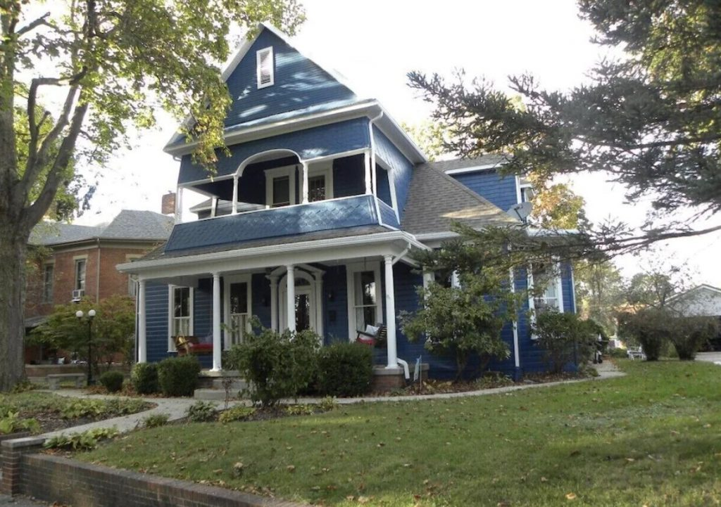 The exterior of a historic home in Logan Ohio. It is a pretty dark blue with white trim. There is a small front porch and a covered deck on the top floor over the front porch. The house has a grassy lawn and shrubs around it.
