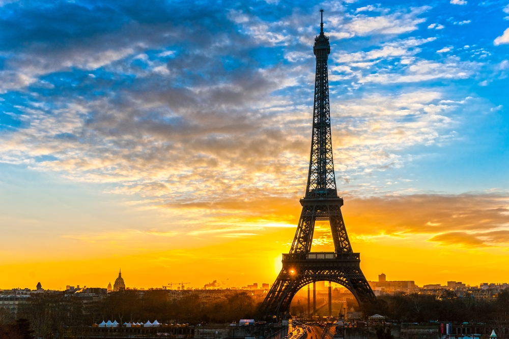 Bright yellow sunset sky with wrought iron Eiffel Tower in foreground.