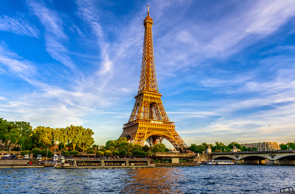 Eiffel Tower with blue waters in foreground and blue sky in background