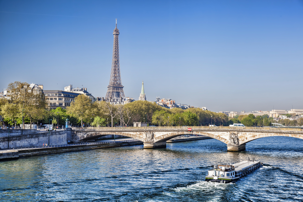 Passenger boat cruising down river, going under ornate arched bridge with Eiffel Tower in background. Perfect for 4 days in Paris itinerary