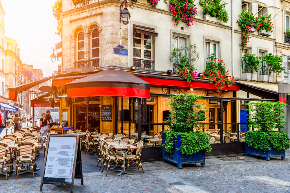 Pretty building with red awning on cobblestone street with menu sign and lush greenery and matching beige and brown tables and chairs.
