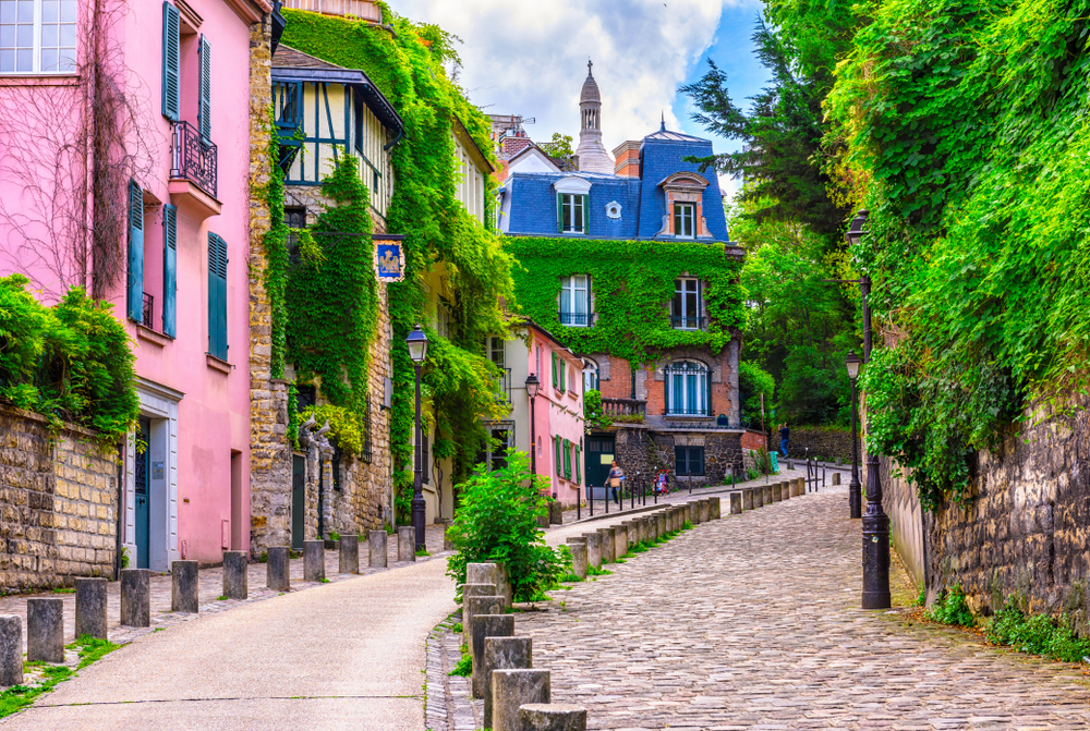 Cobblestone street with colorful houses and roofs and walking path on left. 4 days in Paris itinerary.