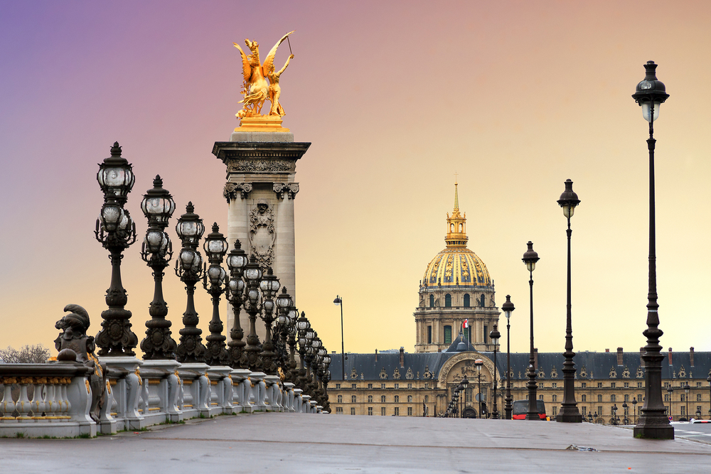 Bridge with ornate black lampposts with white bulbs, ornate building with dome and yellow sunrise sky in background.