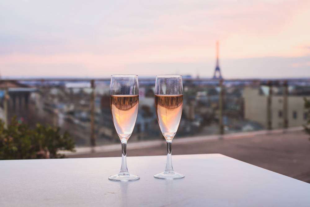 Two glasses of champagne on gray table with blurred Eiffel Tower in background. 4 days in Paris itinerary