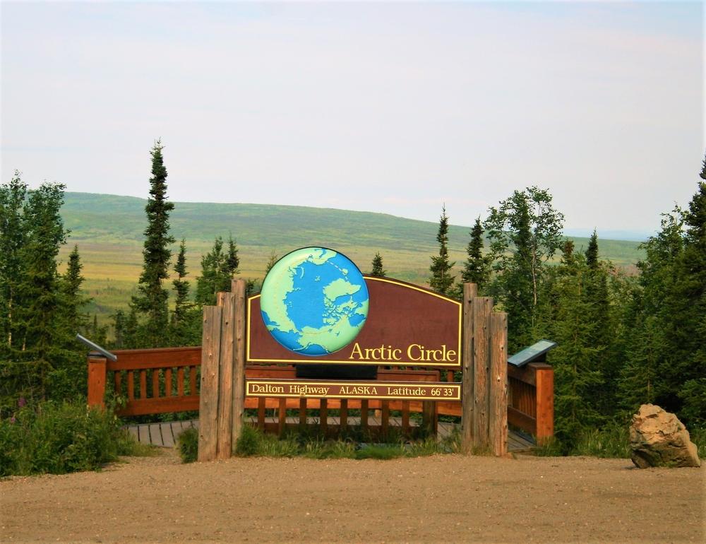 Wooden sign signaling the Arctic Circle with large blue globe and words Dalton Highway ALASKA itinerary Latitude 66'33