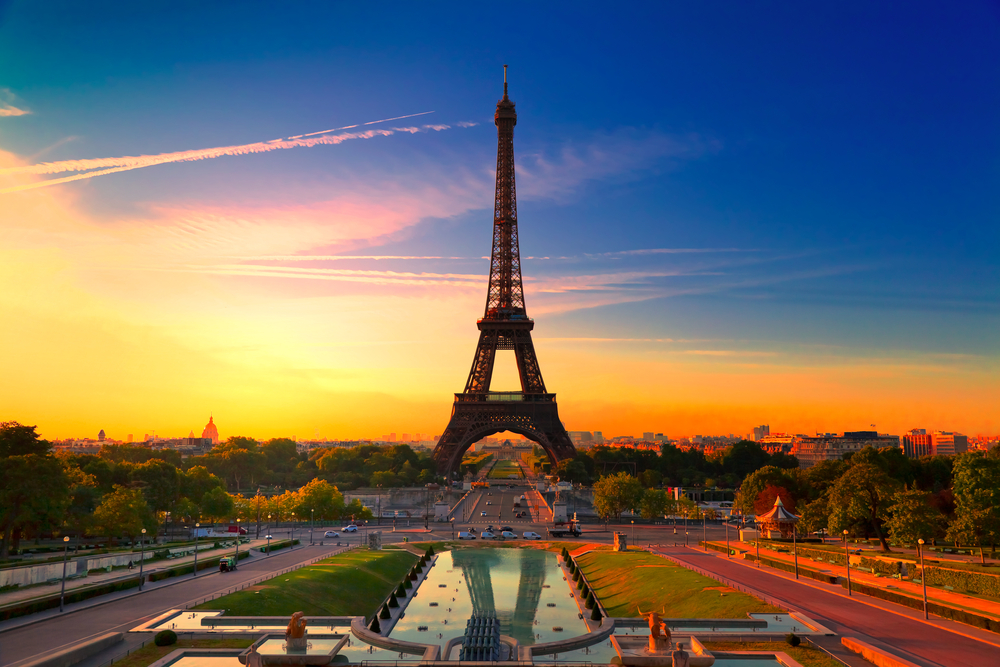 Iron Eiffel Tower at sunset with red and orange sky, street running through it and wading pool in foreground. First time in Paris.