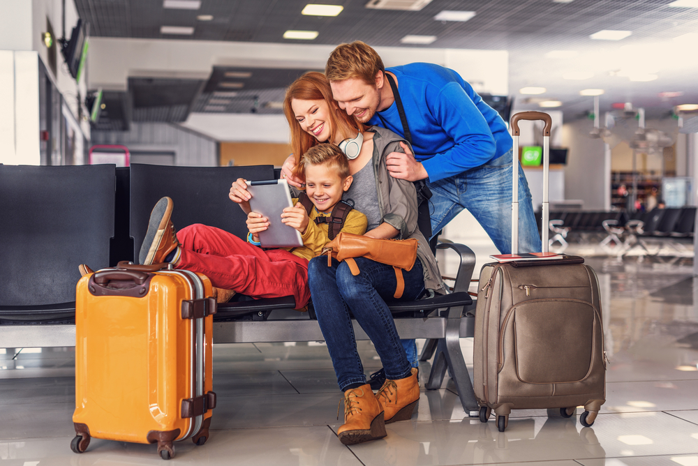 Family of three- caucasian mother, father and son watching screen of personal computer with two carryon suitcases with them. How to pack lightly using only a carryon.