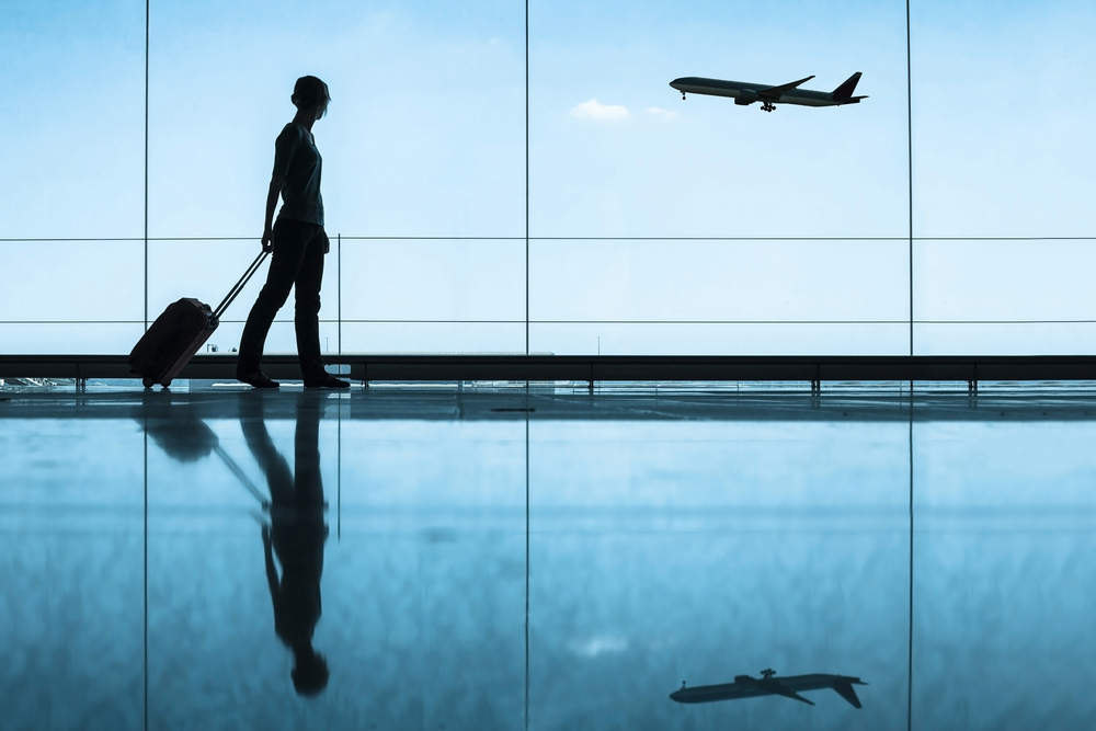 Woman walking past wall of glass windows with plane taking off in background, pulling carry-on suitcase.  How to pack lightly using only  a carry-on.