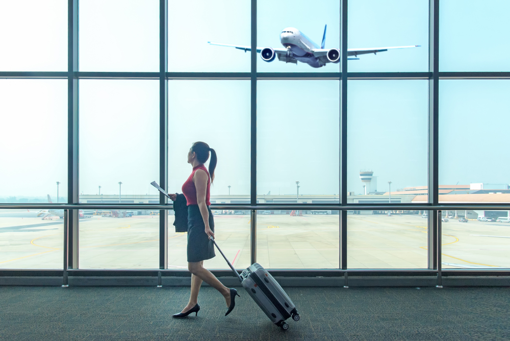 Woman walking next to wall of glass windows with airplane taking off, carrying papers pulling silver carryon suitcase. How to pack lightly in a carryon.