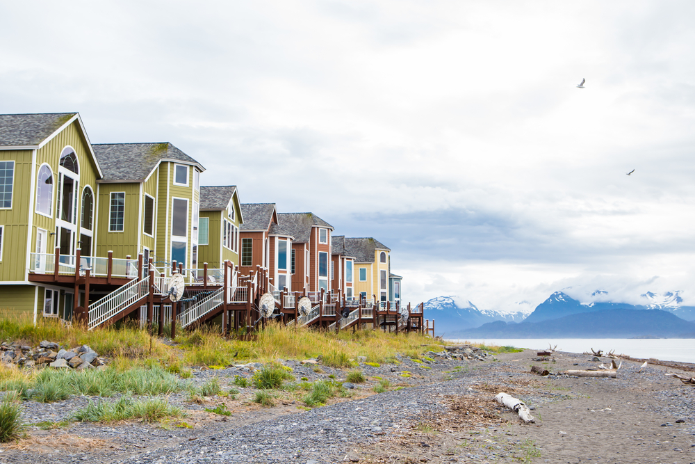 Colorful houses on stilts with pebbly beach in foreground and Alaska mountains in background.