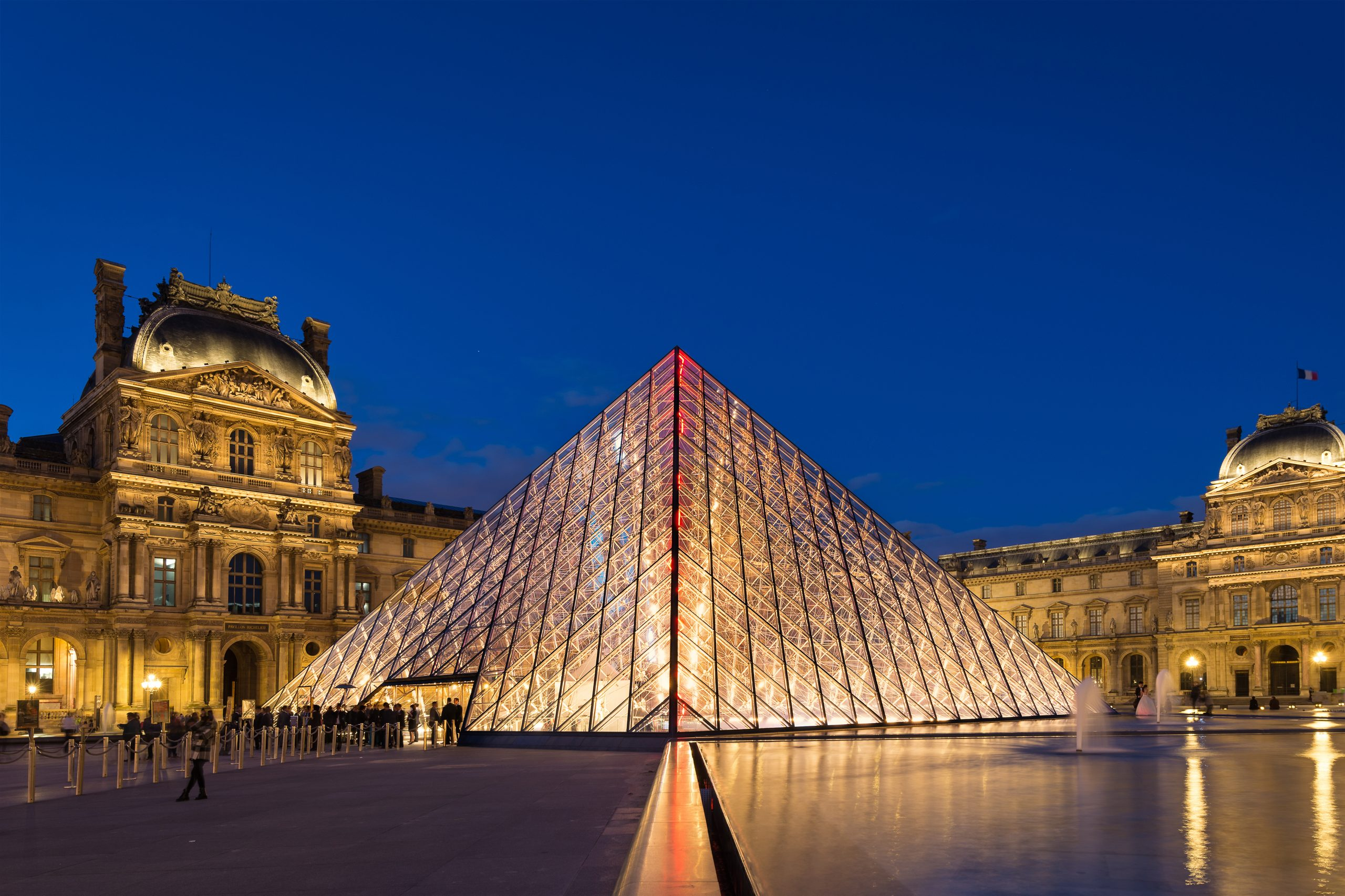 Illuminated glass pyramid with ornate building in background.