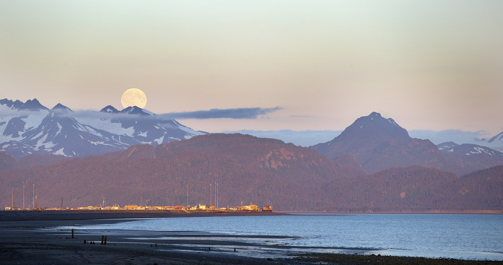 Moon in sky over snow-capped mountains, with town and beach in foreground.