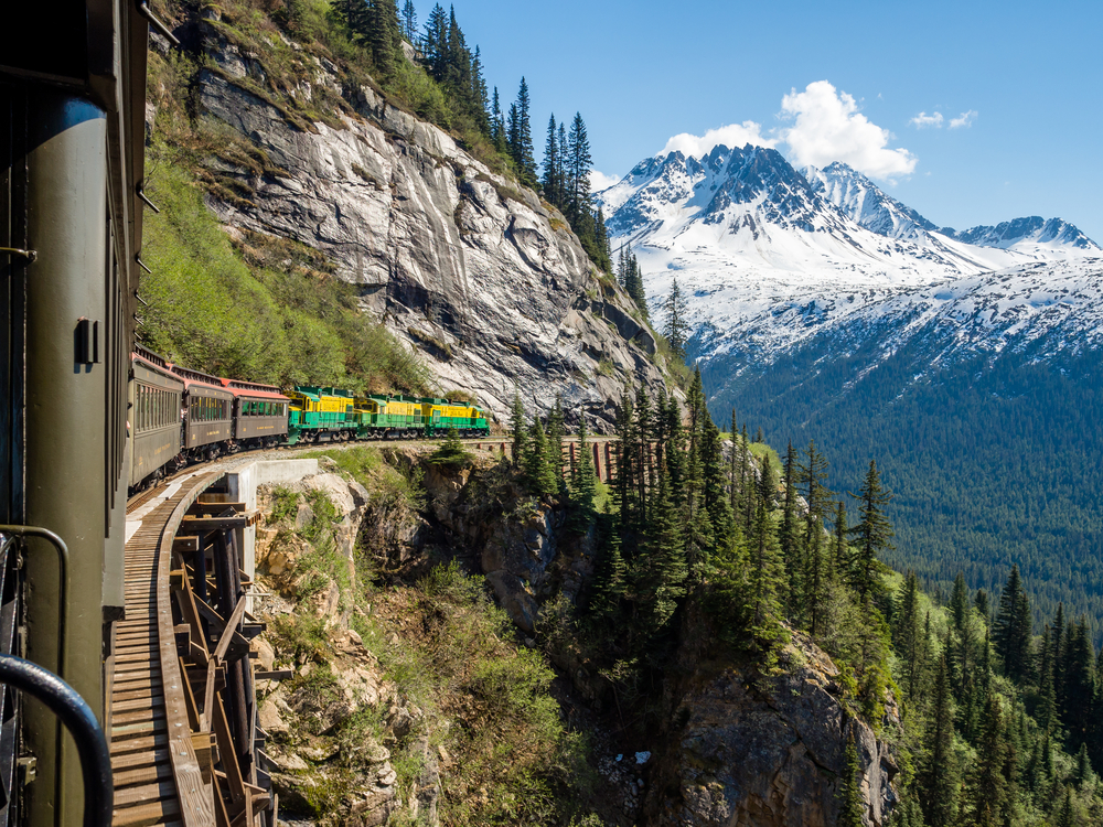 Colorful train on side of mountain with snow-capped mountains in background. Evergreen trees in foreground. Traveling to Alaska