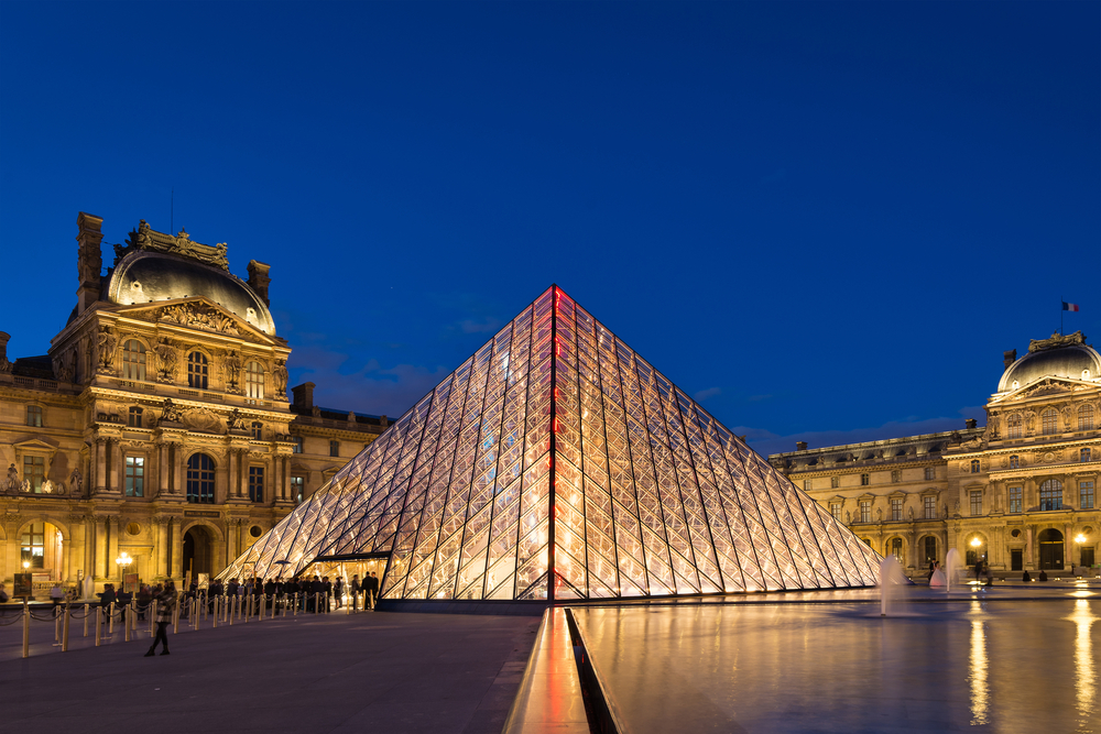 Glass pyramid and opulent buildings in background illuminated at night.