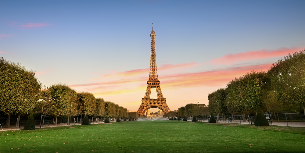 Iron Eiffel Tower with large green  grass in foreground and trees trimmed along both sides of photo.