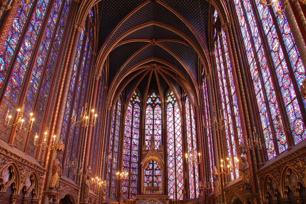 Stained glass windows to ceiling and golden walls with gold lit candleabras