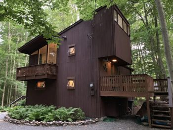A tall dark brown wood paneled cabin in Pennsylvania. There are multiple levels with lots of windows and decks. The cabin is surrounded by trees.