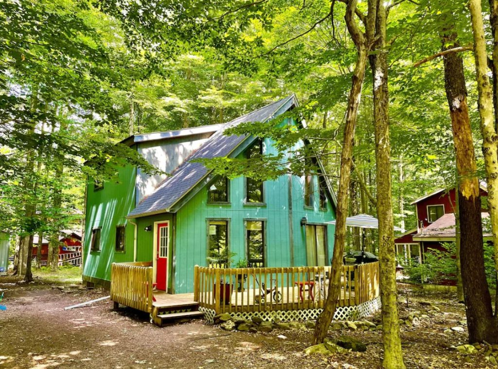 A bright blue large, kind of A-frame, cabin in the woods. They cabin has lots of windows, a large deck, and a bright red door. You can see a few other buildings nearby.